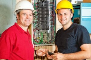 4685123-friendly-master-electrician-and-apprentice-working-on-breaker-panel